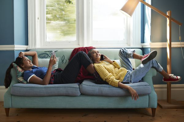 Two people sitting on a sofa smiling while looking at their smartphones