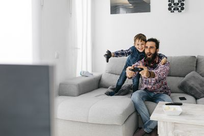 A man and boy sit on a sofa holding games controllers. They're smiling and cheering