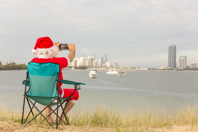Santa in a folding chair, talking a picture of a city skyline.