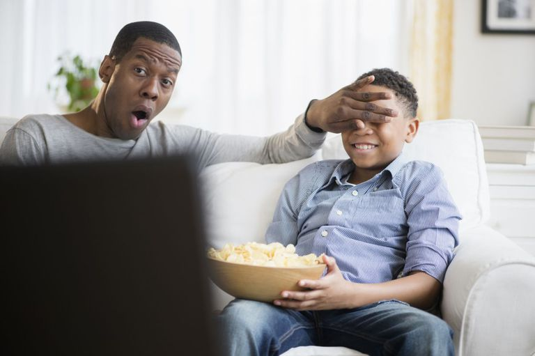 Dad covering son's eyes on couch while they watch TV
