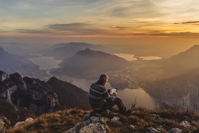 Man hiker solo on the mountain during golden hour reading Nook book on Kindle Fire tablet
