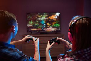 Two people playing PlayStation games on a TV.