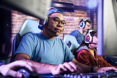 A man sitting at a desk wearing a gaming headset and holding a gaming mouse