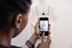 A shopper using an iPhone to photograph a purse