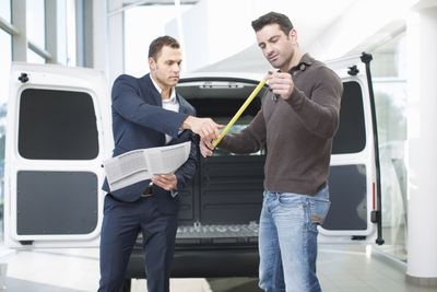 Two men in front of a van with a measuring tape