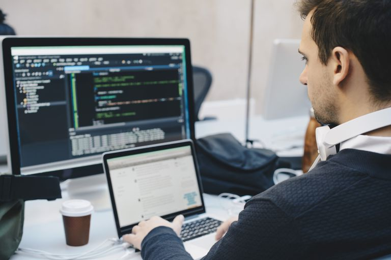 Man working on two computers with CSS HTML code on the screen