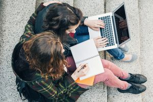 Two university students taking notes on a paper notebook and a laptop