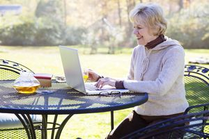 Senior woman smiles while using laptop outside sitting on patio furniture