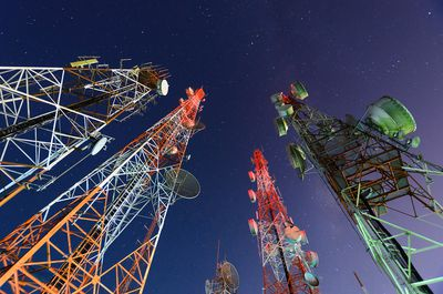 Five telecommunication towers under a night sky