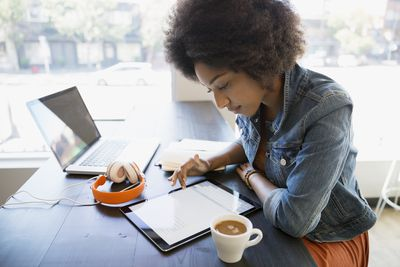 Focused woman working at digital tablet in cafe