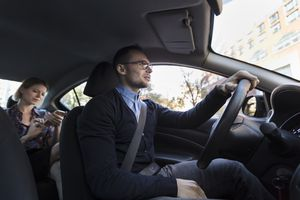 Man driving car for Uber or Lyft rideshare with woman in the back seat looking at her phone