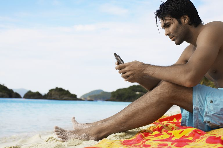 Young man using mobile phone on beach (low angle view), St. John, US Virgin Islands, USA