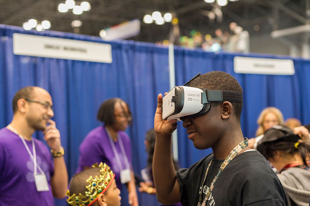 A visitor to the Comcast NBCUniversal booth wears a Samsung Gear VR Virtual reality device at a Career Expo held at the FIRST Robotics NYC Championship
