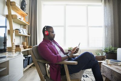 Man with headphones and mp3 player listening to music in living room
