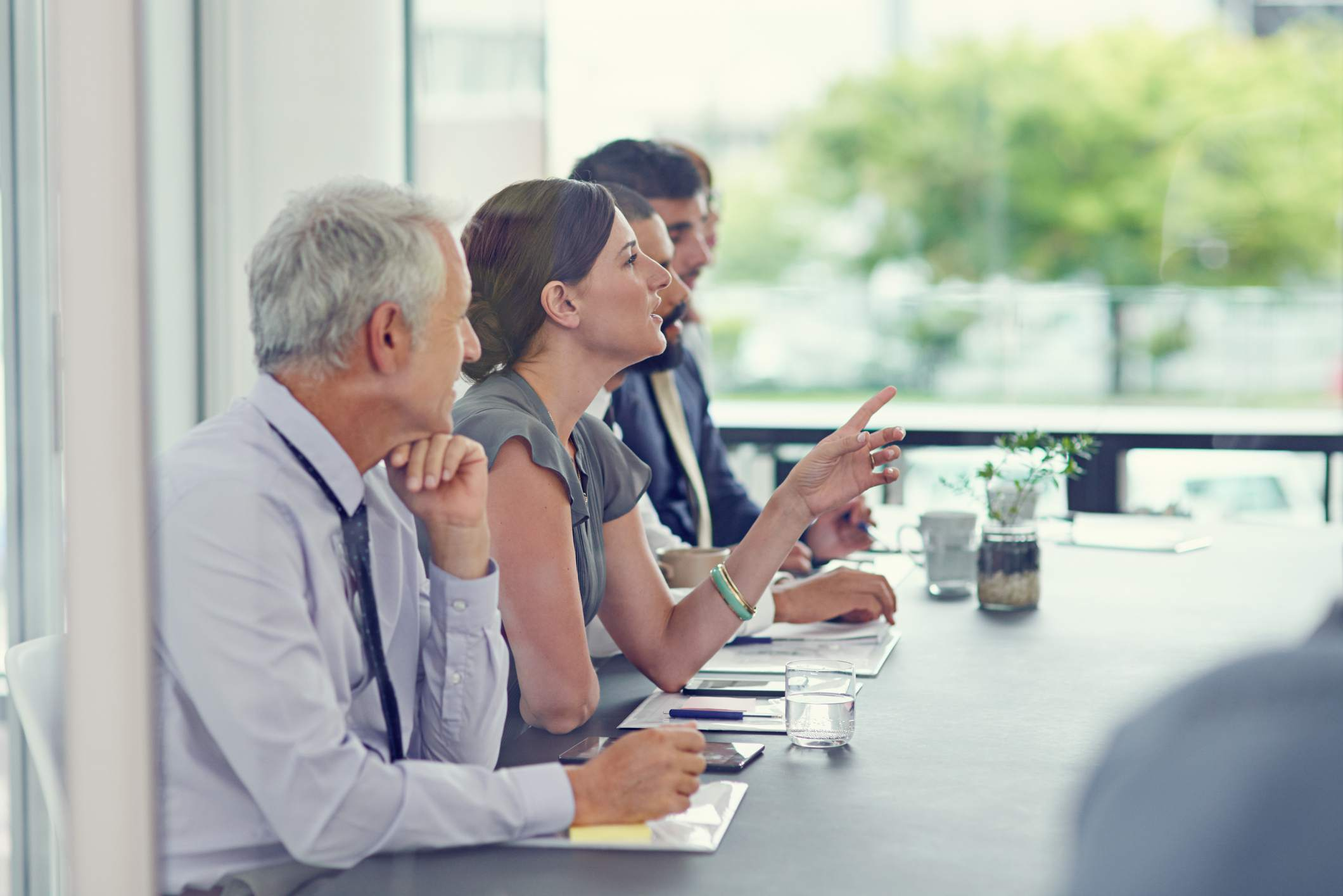 Group in conference room, woman talking in and pointing