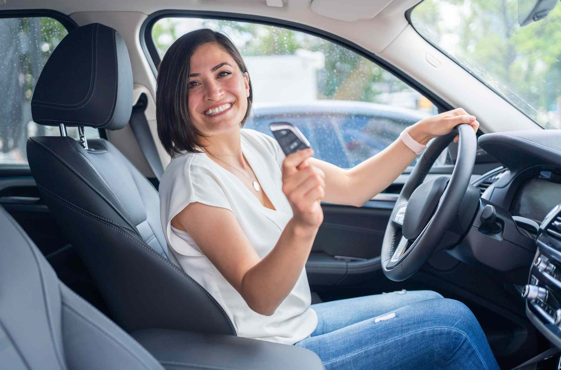 Woman in driver's seat holding car key of her new electric car