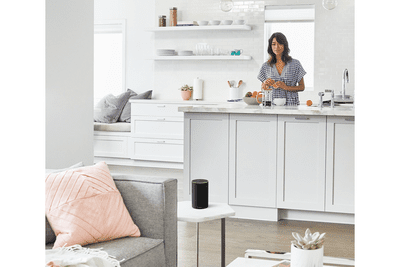 A woman using her Amazon Echo device in her kitchen.