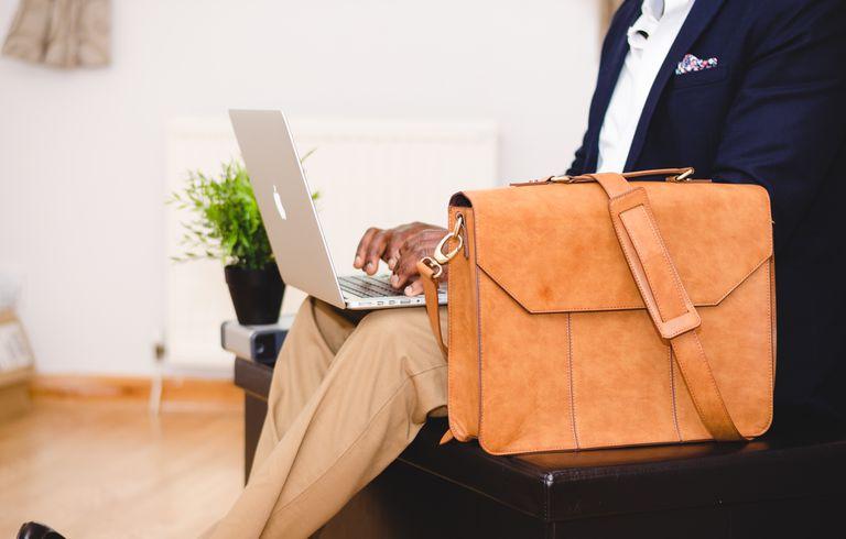 Man using laptop beside bag