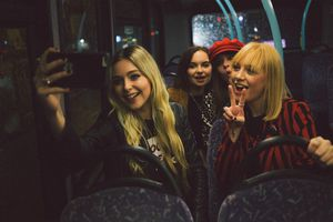 A group of friends taking a selfie on a bus.