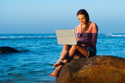 Woman using laptop on the beach