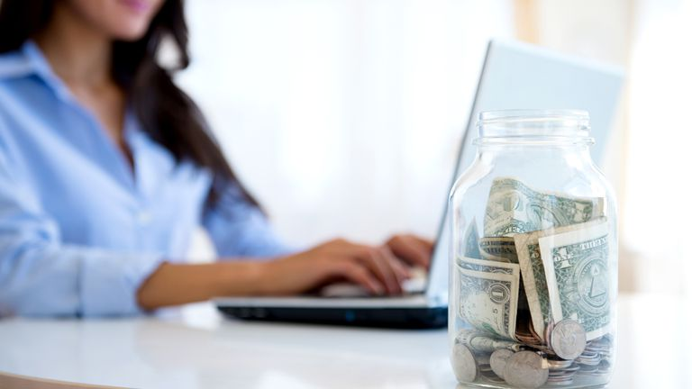Woman in blue shirt working on a laptop computer with a glass jar of money next to her