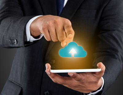 A photo illustration showing a man holding a smartphone while a drawing of a cloud is meant to represent data uploading from the phone to offsite storage.