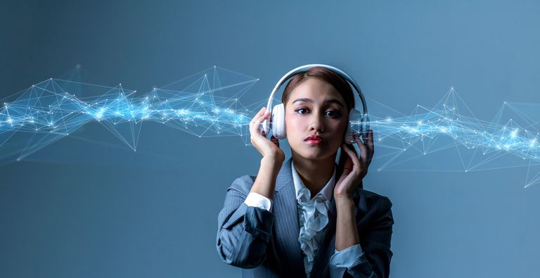 A woman listening to headphones as wireless signals float by