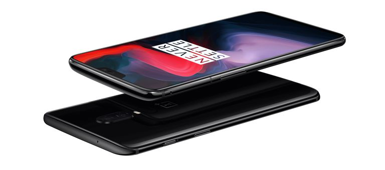 Two OnePlus 6 smartphones, one facing up and one facing down. The screen says