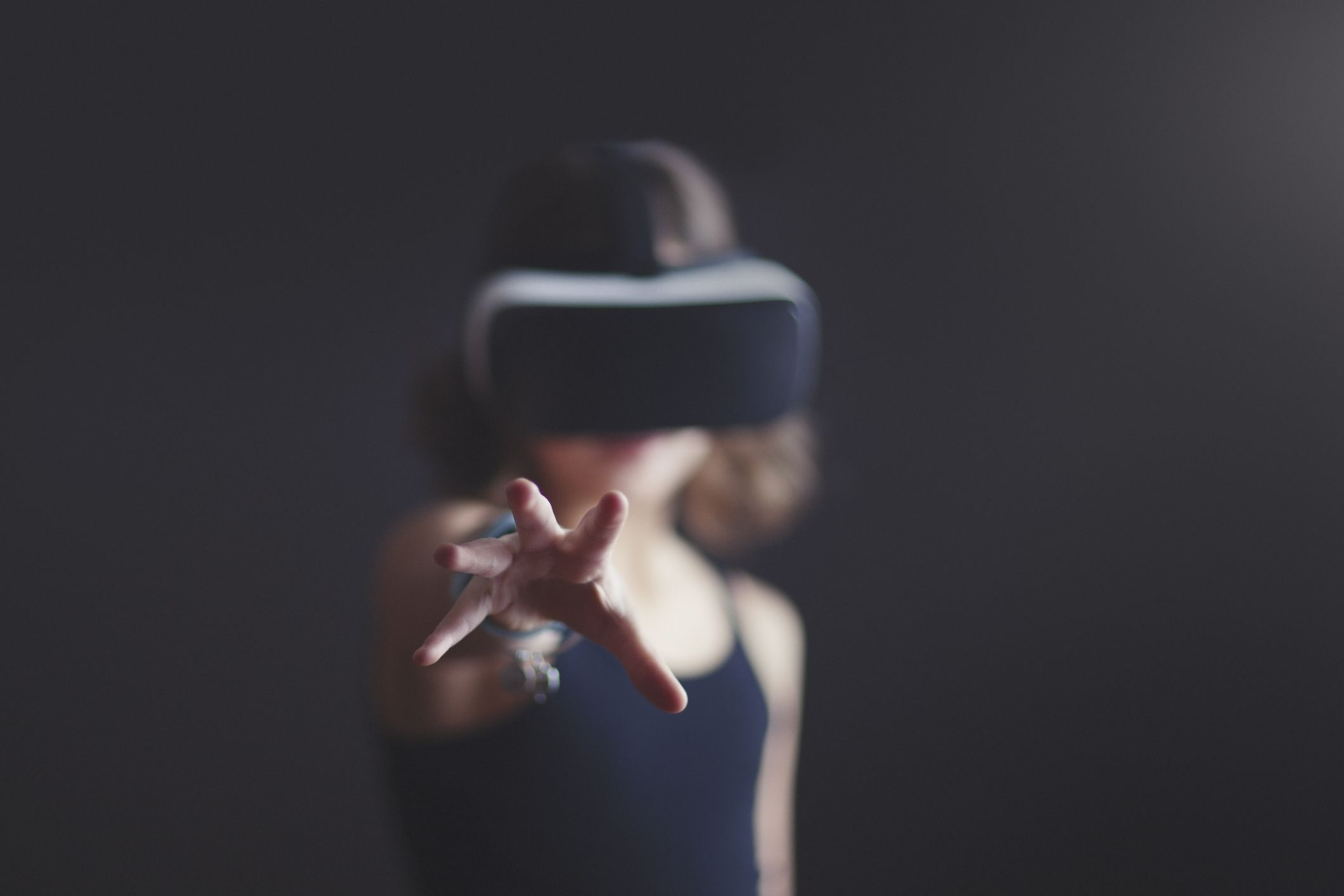 Someone wearing a VR headset reaching toward the camera.