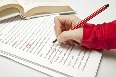 Picture of someone proofreading a paper with red ink