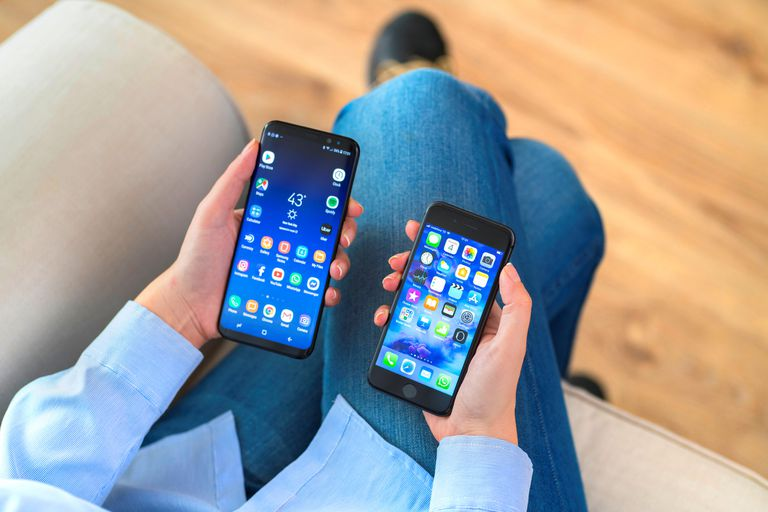 Person holding 2 different android cell phones