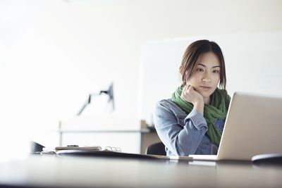A graphic designer using a laptop at a desk