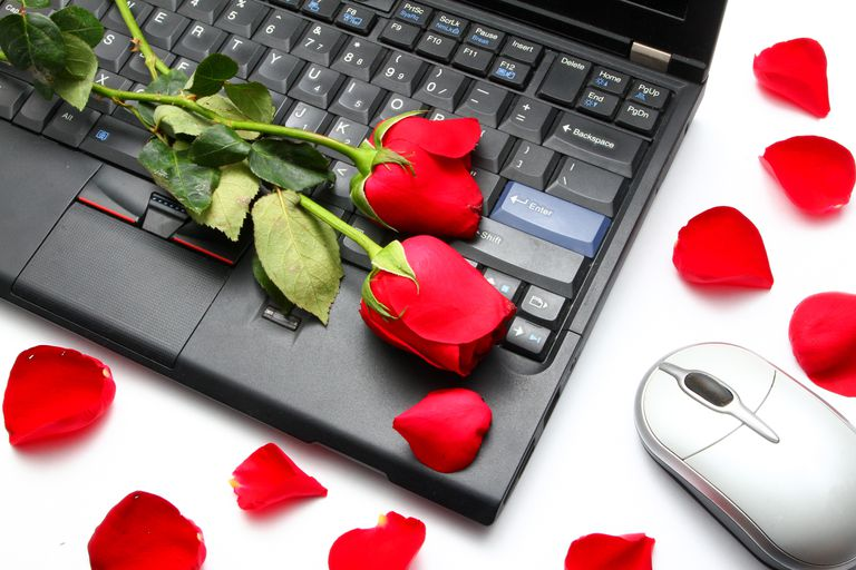 High Angle View Of Red Roses On Laptop