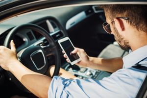 Man in driver's seat of car using smartphone.