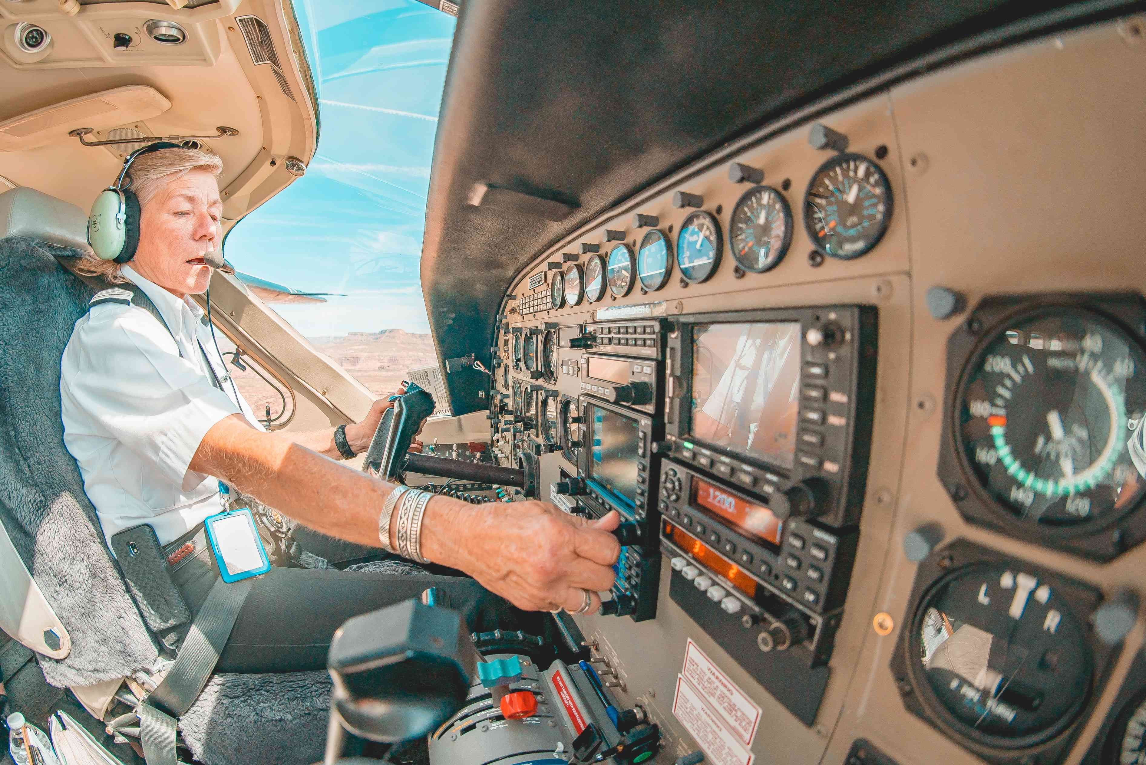 A pilot in a cockpit flying a plane over the grand canyon.
