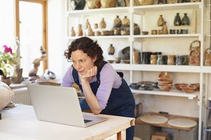 Woman leaning over looking at laptop