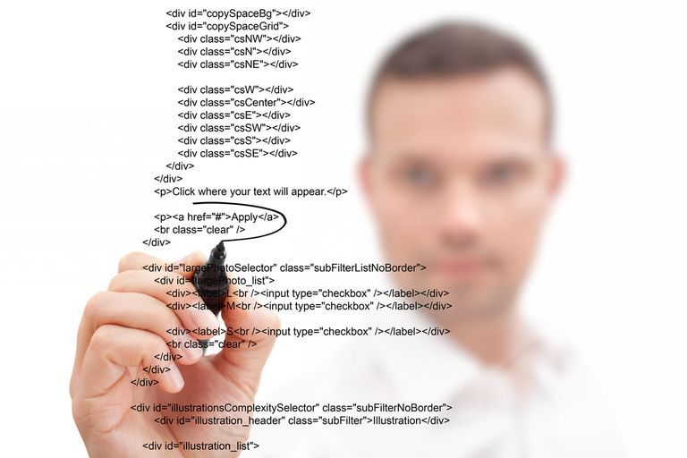 Man blurred in the background editing HTML on clear surface.