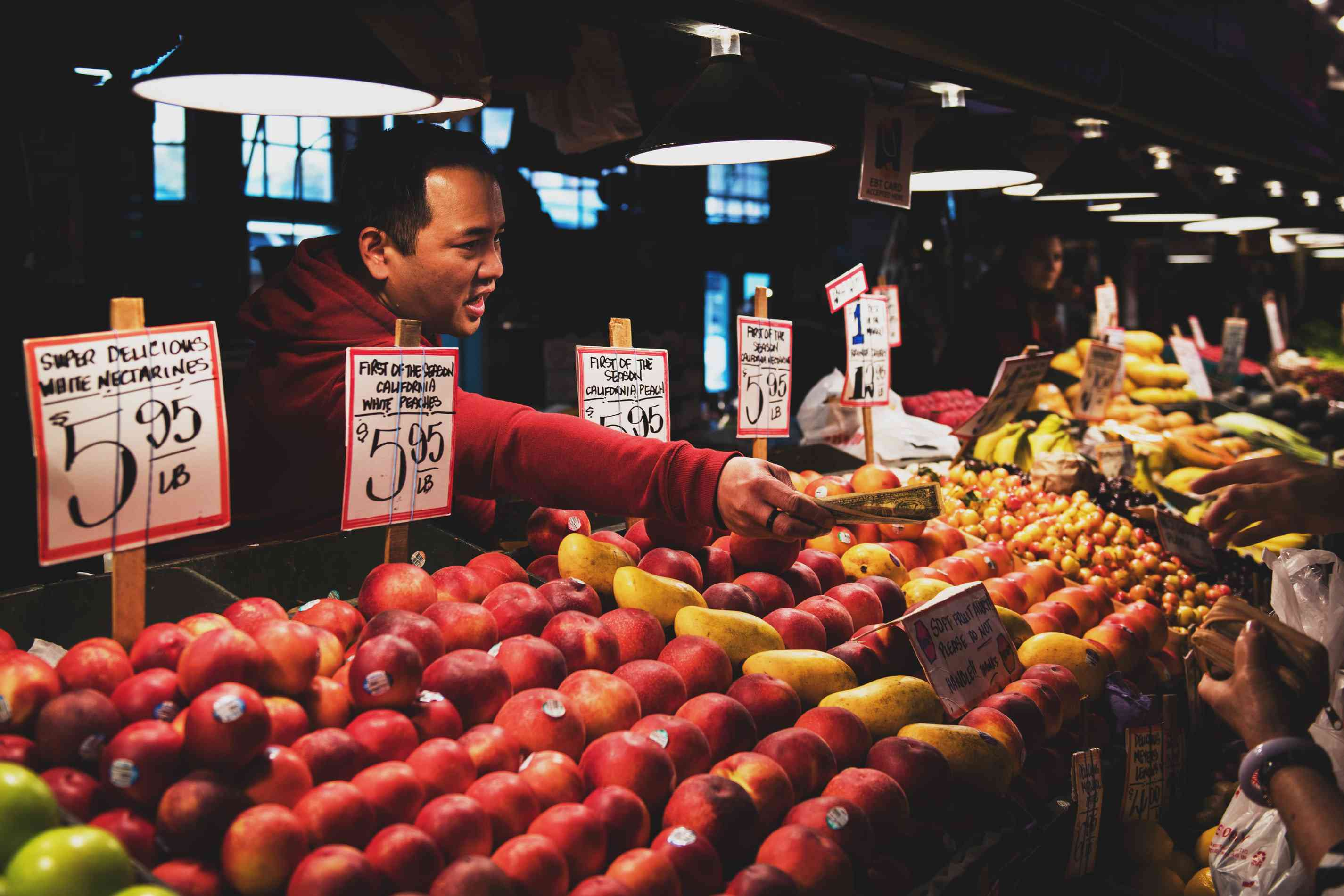 man selling fruit while talking to people off camera