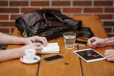 Two people sitting at a cafe table, with their iPhones and an iPad, one writing in a notebook.