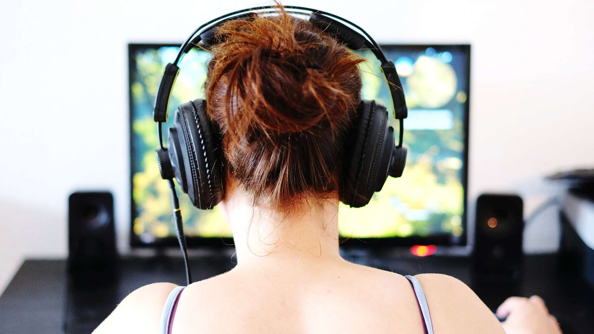 Person with headphones on playing a video game on a computer.