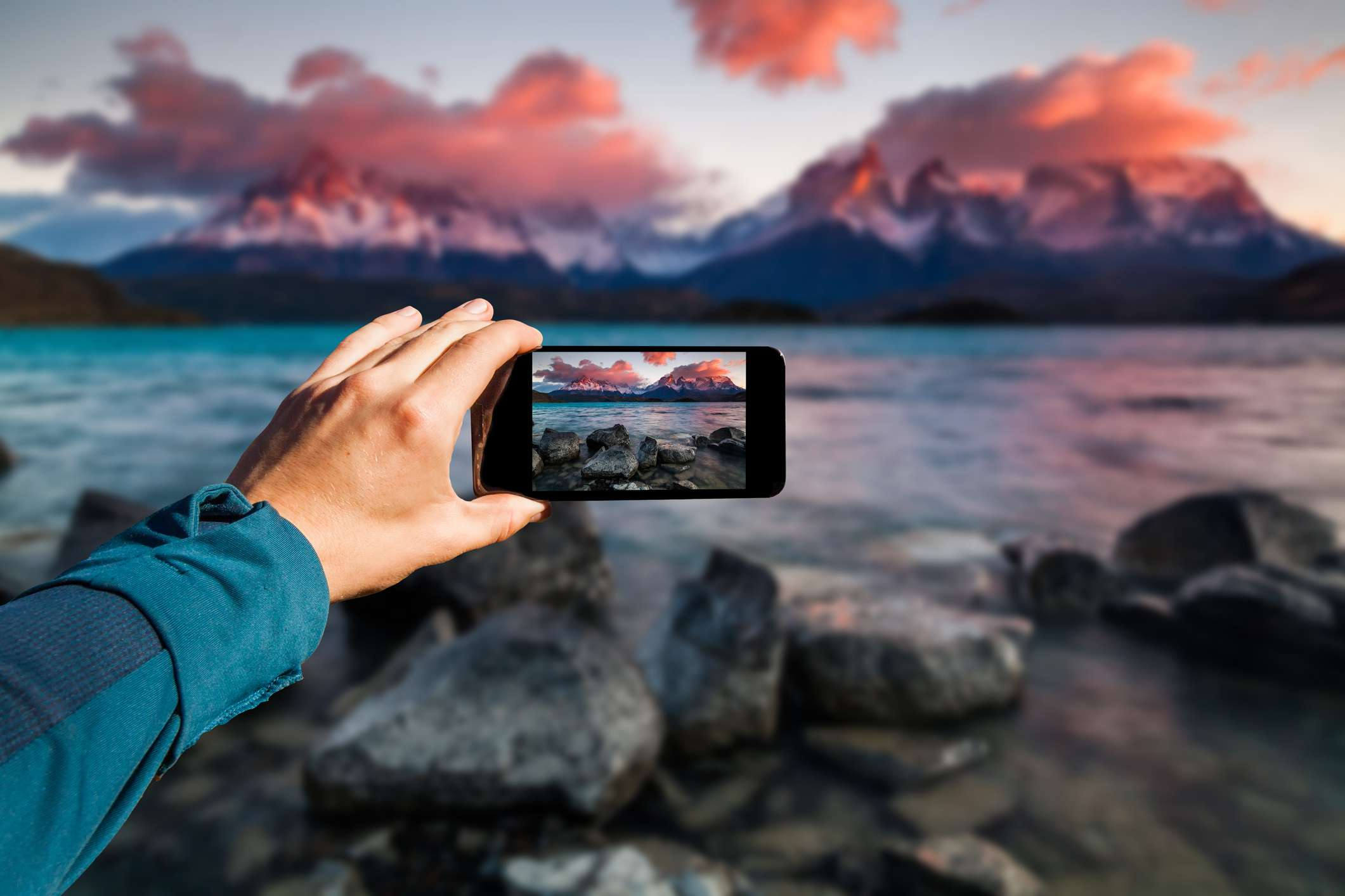 Someone taking a sunset picture of a lake with mountains in the bacground on a smartphone.