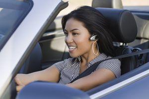 Asian woman driving convertible car