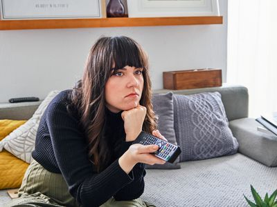 A woman sitting looking bored at an off-screen TV while holding a remote control