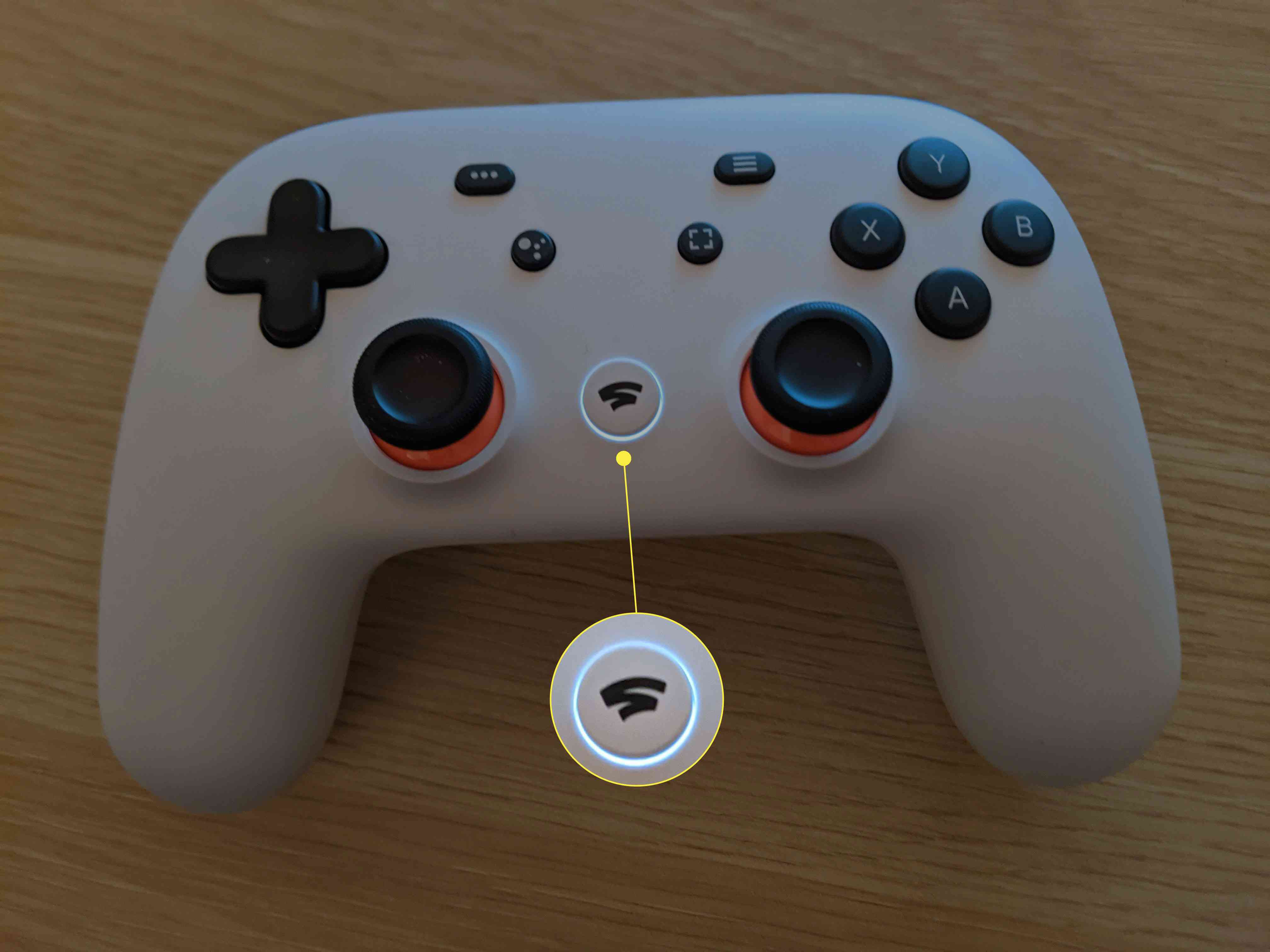 A Stadia controller with the Stadia button flashing white.
