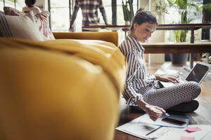 Freelancer working at laptop on living room floor