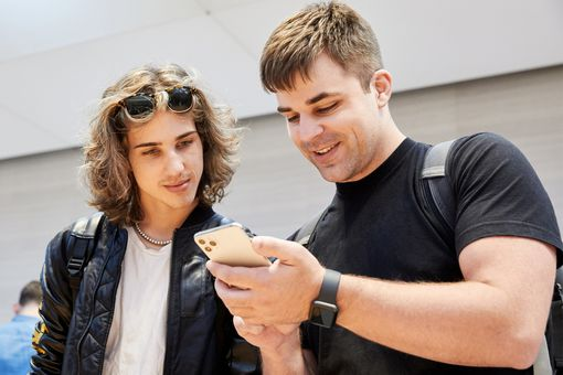 Two men at an Apple Store using an iPhone 11.