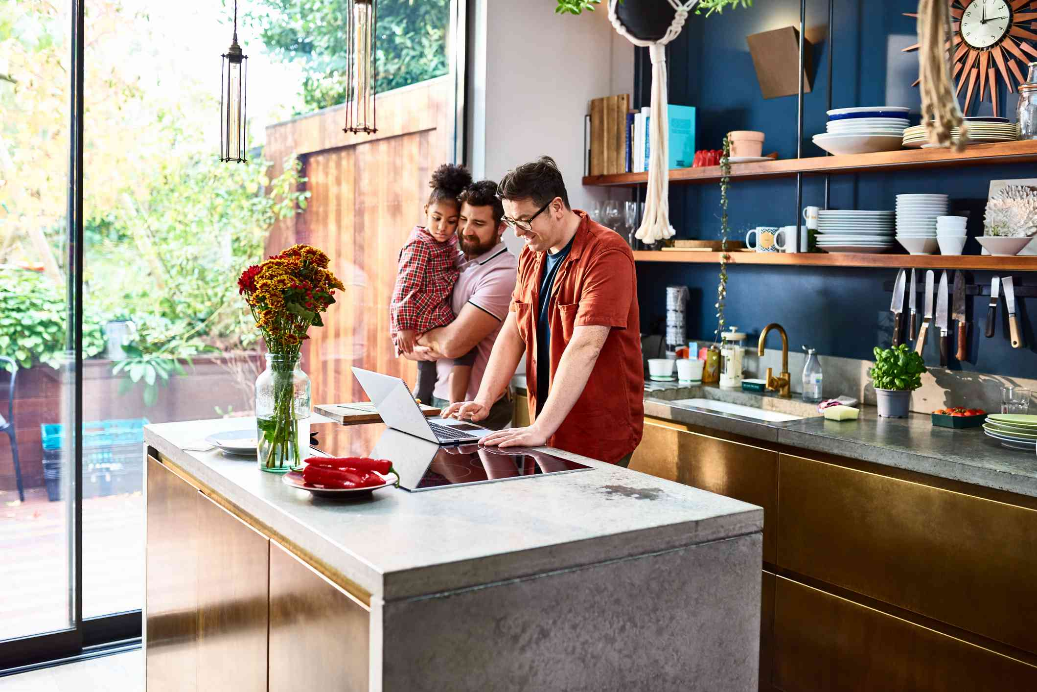 A couple, one holding a child, looking at a laptop in the kitchen of a home.