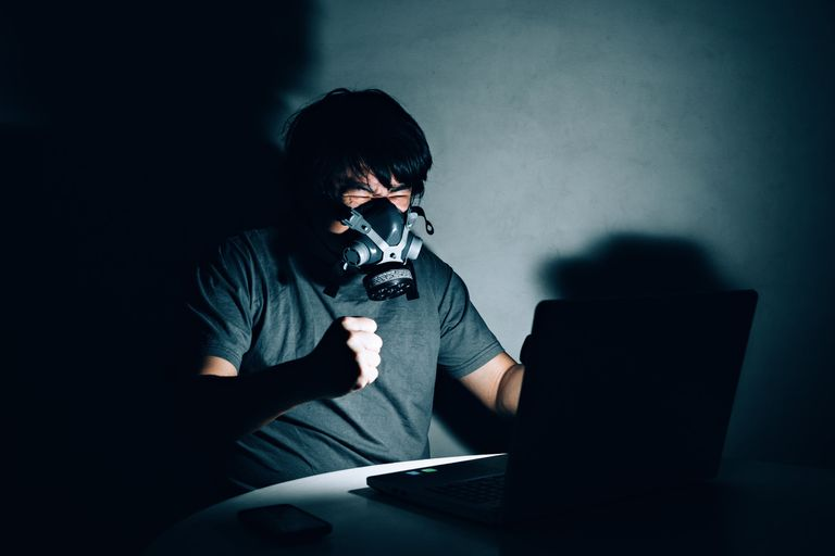 Man wearing gas mask and working on computer