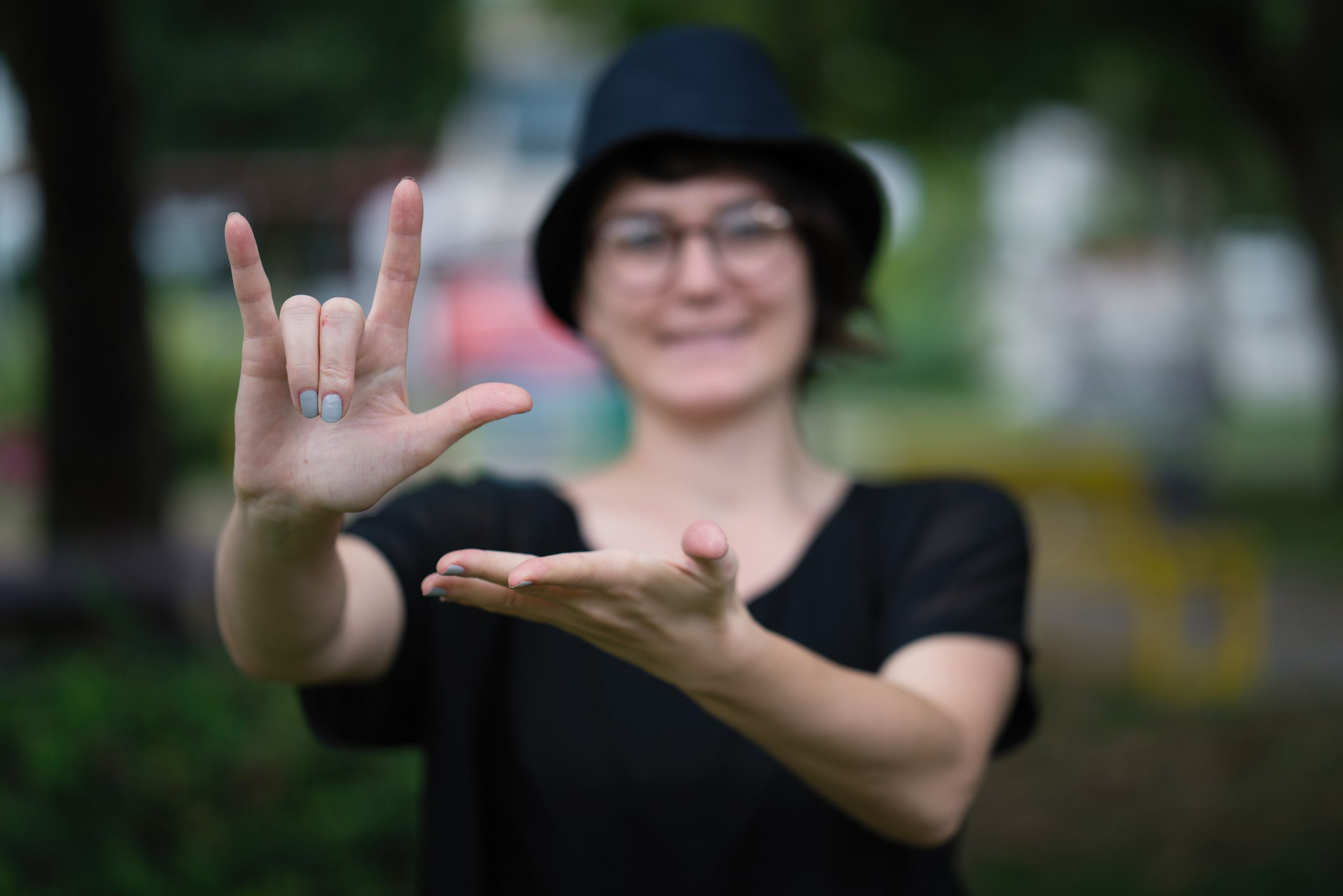 Someone showing a sign language sign in an outdoor setting.
