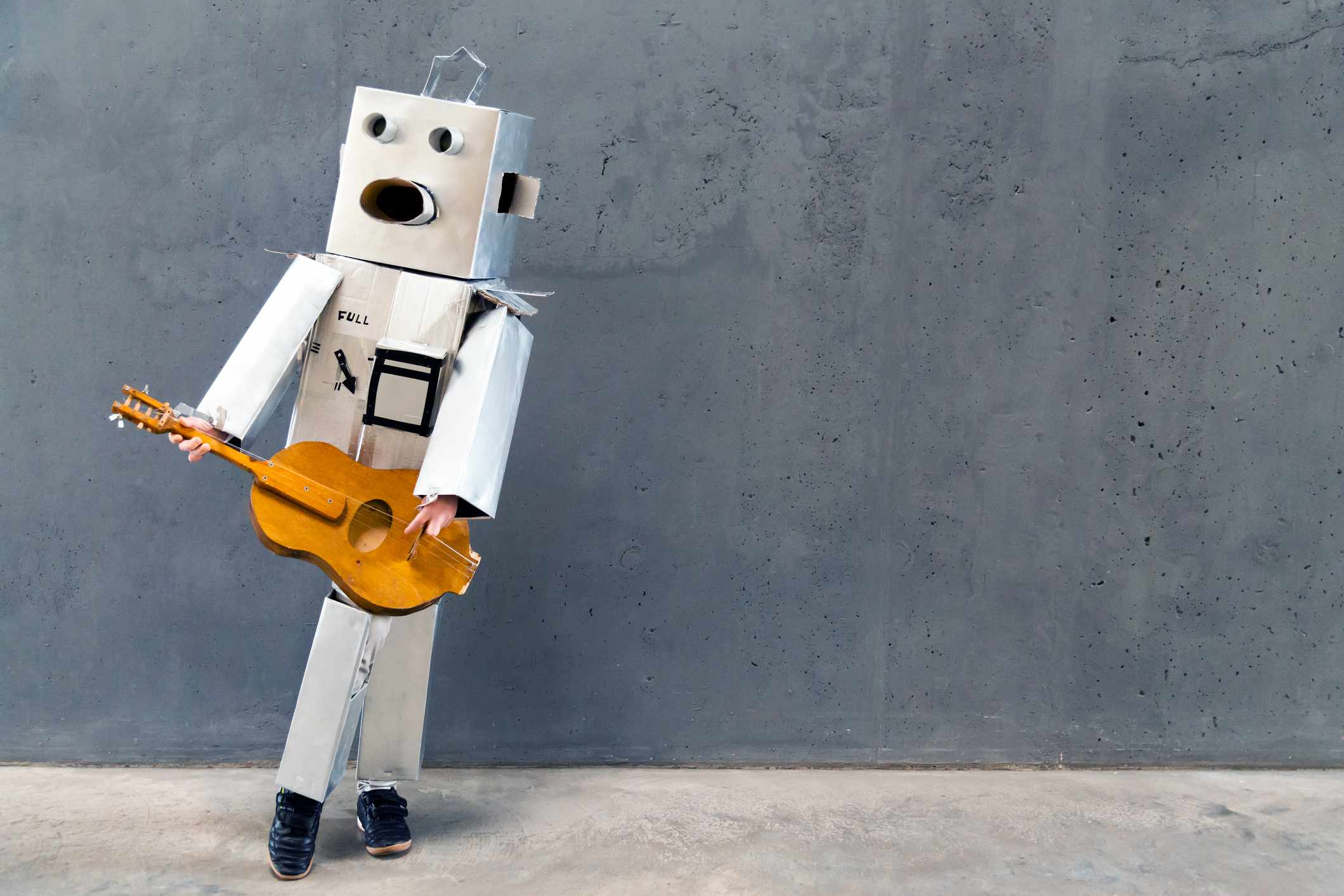 Homebuilt robot playing guitar in front of concrete wall - Artificial intelligence concept
